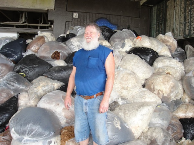 Man in front of these bags filled with hair!